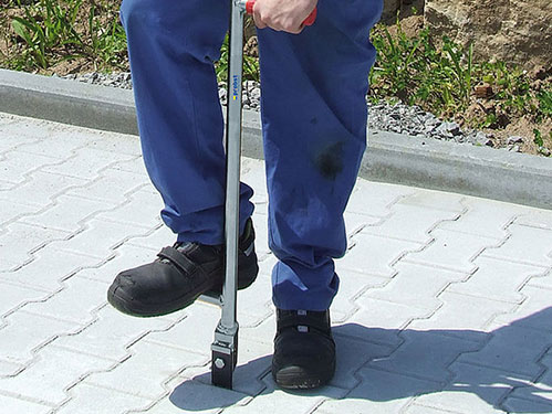 Alignment-Bar tool being use to align pavers in order. Probst Paving Tools
