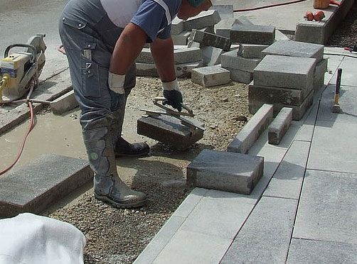 Slab-Handle being used to lift concrete paver instead of hands